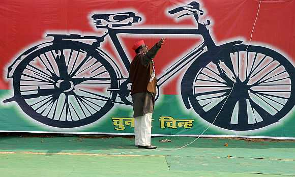 A Samajwadi Party worker gestures in front of a banner with the party's electoral symbol in Allahabad