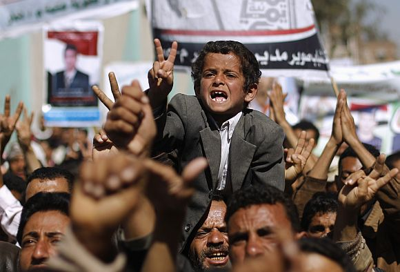 A boy shouts slogans with anti-government protesters as they march to demand the release of detained fellow protesters in Sanaa