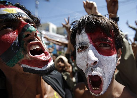 Anti-government protesters with their faces painted in colours of flags of Egypt, Tunisia, Kingdom of Libya and Yemen shout slogans during a rally to demand the ouster of Yemen's President Ali Abdullah Saleh in Sanaa