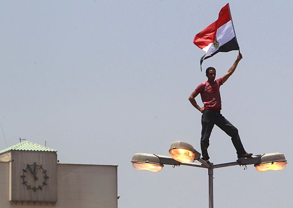 A protester holds an Egyptian flag while standing on a light pole at Tahrir square in Cairo