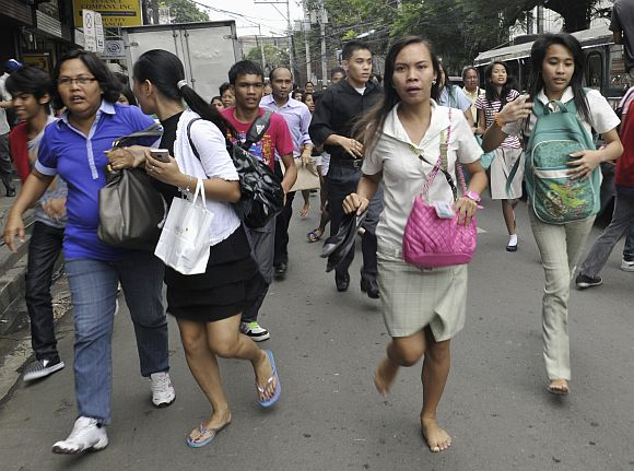 Workers and students run after they feel the earthquake along a main street of Honkera, Cebu city, central Philippines