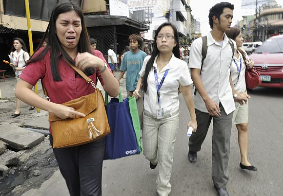 A woman cries after experiencing the earthquake along a main street of Honkera, Cebu city, central Philippines