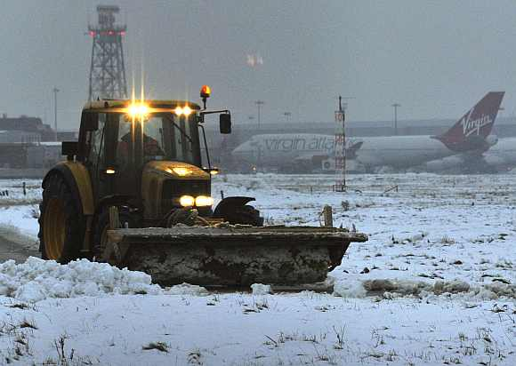 Snow is cleared from the southern runway at Heathrow airport in west London