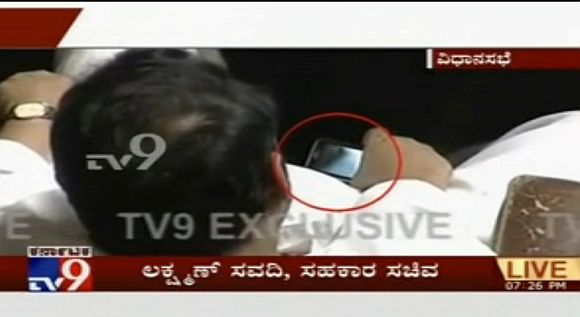 Lakshman Savadi caught watching a clip on a mobile phone