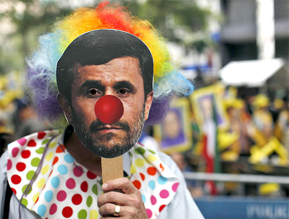 A protester wears a mask depicting Iran's President Mahmoud Ahmadinejad