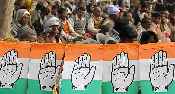 Supporters of the Congress party sit next flags of party's logo in Gorakhpur
