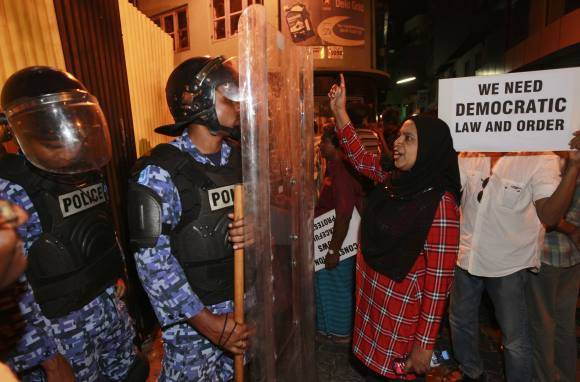 Police officers look on as demonstrators call for the release of Criminal Court Chief Justice Abdulla Mohamed, in Male.