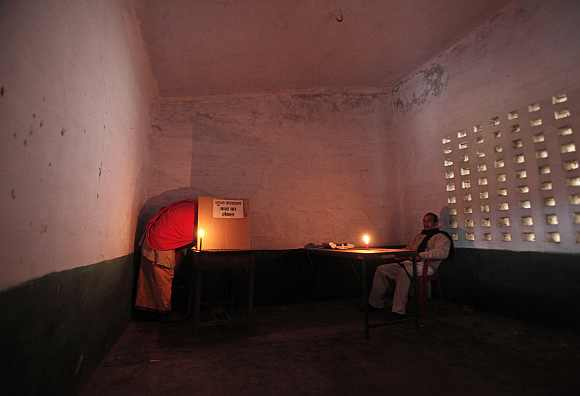A priest  casts his vote as a polling officer watches at a polling station in Ayodhya