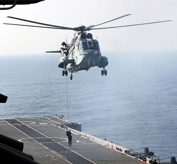 A naval commando slithering from a Sea King helicopter