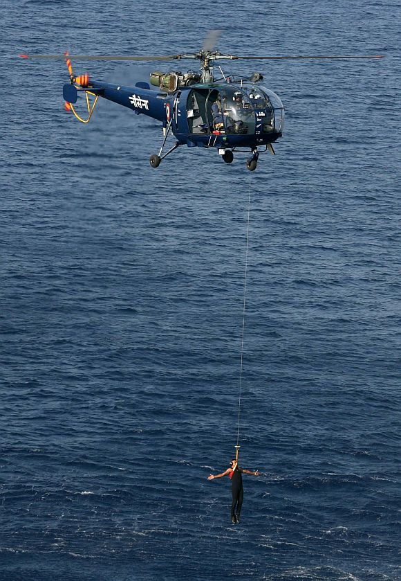 An Indian Navy helicopter demonstrating a rescue at sea