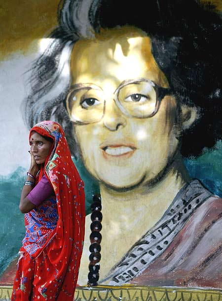 A woman passes a painting of Indira Gandhi in Kolkata