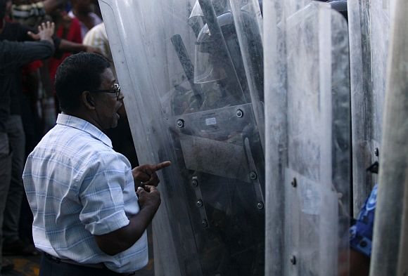 A supporter of ousted Maldivian President Mohamed Nasheed argues with the riot police during a clash in Male
