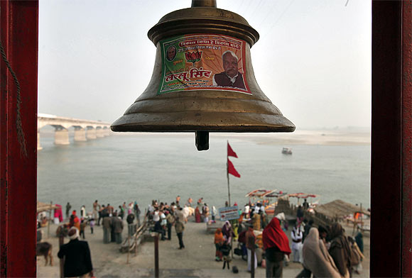 A temple bell pasted with a pamphlet of the BJP is seen on the banks of Saryu