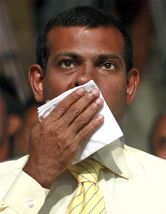 Former Maldivian president Mohamed Nasheed wipes his face during a Maldivian Democratic party meeting in Male