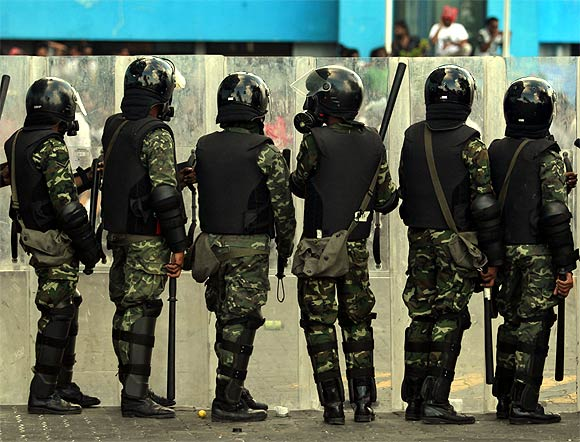 Maldivian riot police officers stand guard as they block the supporters of ousted Maldivian president Mohamed Nasheed during a clash in Male