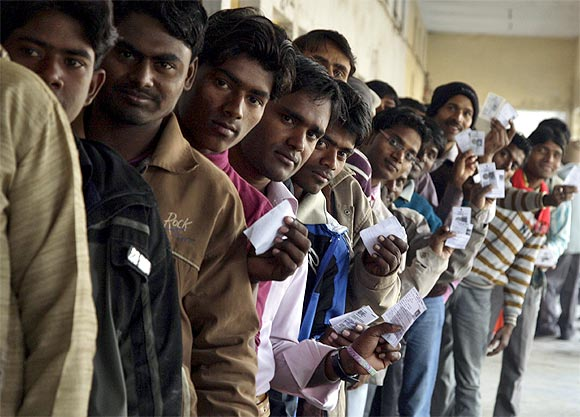 Voters display their voter identity cards as they wait for their turn to cast their ballots