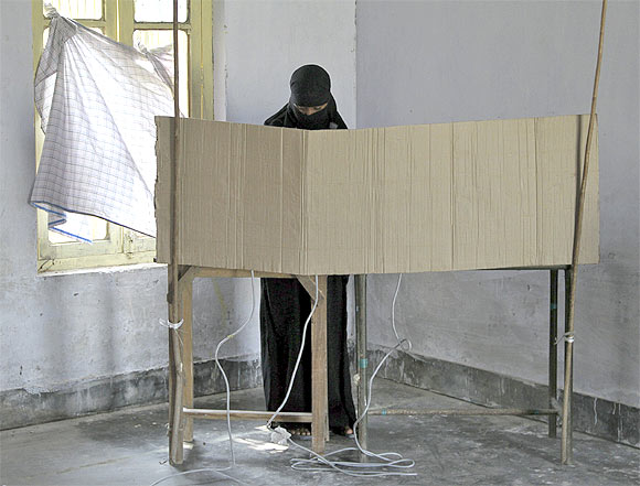 A veiled woman casts her vote at a polling booth