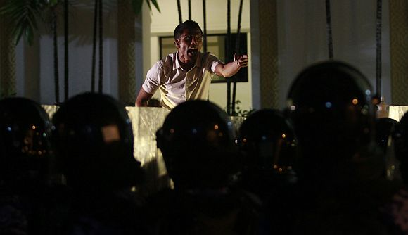 A supporter of Mohamed Nasheed shouts slogans in front of a police officer during a protest in Male on Sunday night