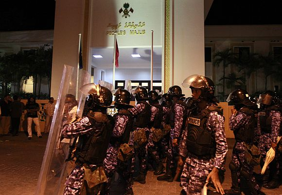 Maldivian police officers walk past the Maldives parliament during a protest, in Male, on Sunday night