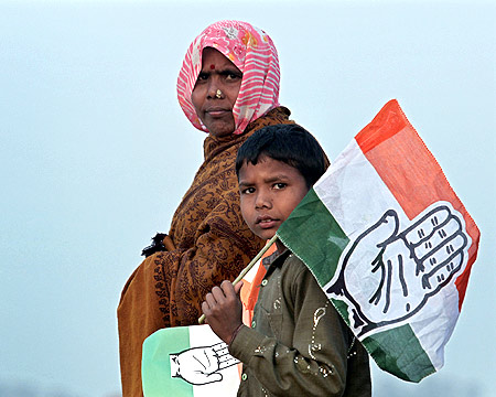 A woman and a child leave after listening to Rahul Gandhi at a campaign rally in Hardoi, UP