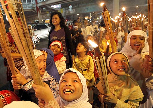 Children march through a street carrying torches to mark the end of Ramadan in Jakarta