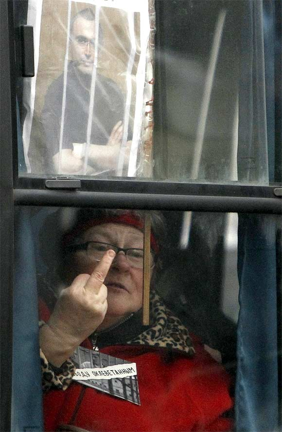 A protester gestures from the window of a police bus in front of the court building in Moscow