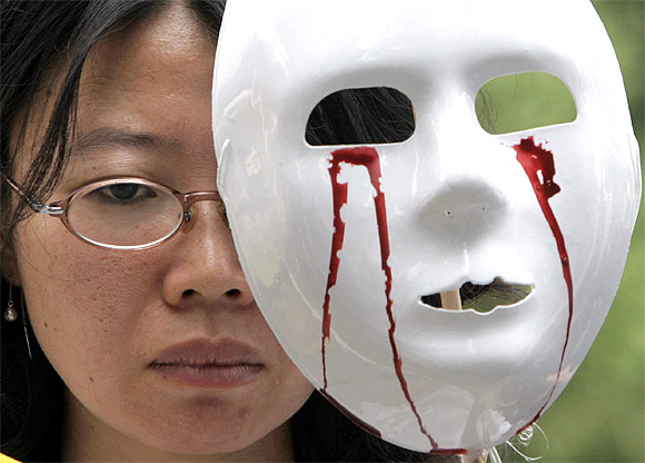 A protester holds a mask during an anti-war rally in Seoul, South Korea