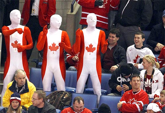 Team Canada fans dance and cheer during a hockey game