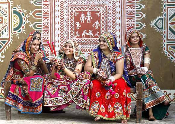 Dancers dressed in traditional attire sit on a cot during Navratri in Ahmedabad