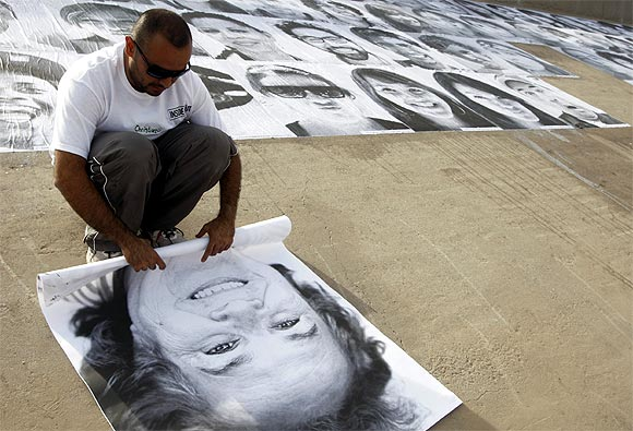 A volunteer rolls up a photograph during an open-air exhibition at Rio Bravo, in Ciudad Juarez, Mexico
