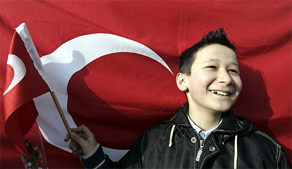 A child waves a Turkish flag during a ceremony to mark National Sovereignty and Child's Day