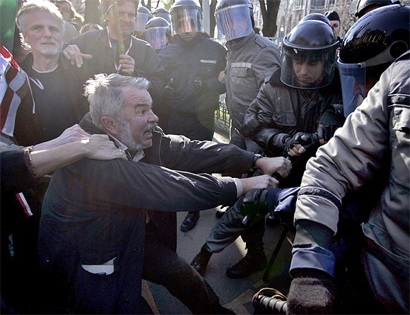 A Hungarian protestor fights with the riot police in front of the parliament in Budapest