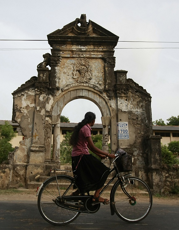 A woman rides a bicycle past a building damaged during the civil war in Jaffna, about 304 km north of Colombo