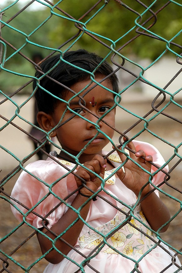 A Sri Lankan refugee girl stands behind the gate of the Mandapam refugee camp in the Ramanathapuram district, about 620 km from Chennai