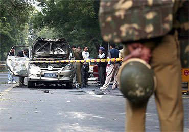 Police and forensic officials examine the damaged Israeli embassy car in New Delhi