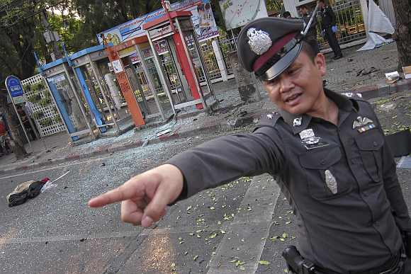 A policeman gestures at the site where a man was injured when a bomb he was carrying exploded, in central Bangkok