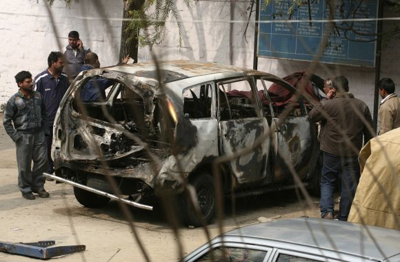 Police cover a damaged Israeli embassy car before it was towed away from a police station to another police station in New Delhi