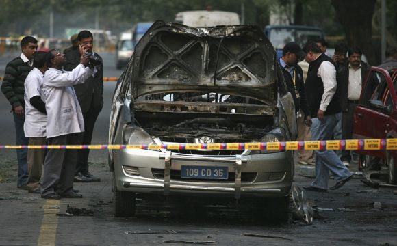 A forensic official takes pictures of a damaged Israeli embassy car after an explosion in New Delhi