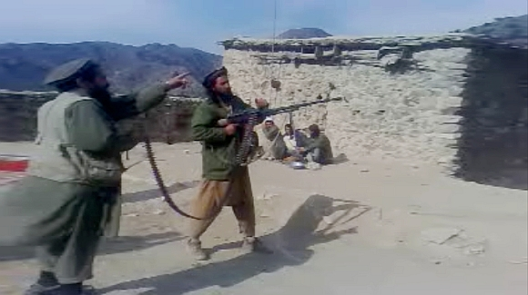 In this undated image taken from a video recording provided by the Pakistan Taliban, men are seen firing a weapon in an undisclosed location in Pakistan's northwest tribal region
