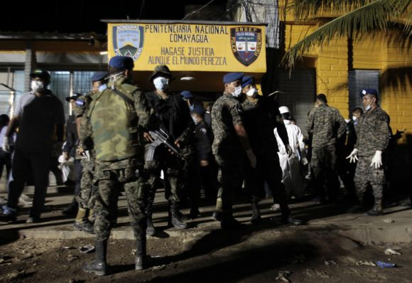 Soldiers stand outside a jail in Comayagua where a massive fire raged through the overcrowded prison in Honduras, killing more than 350 inmates