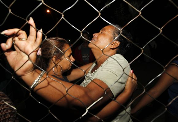 Women cry while standing outside the prison in Comayagua