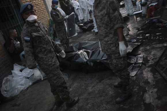 Soldiers stand near body bags bearing dead inmates at a jail in Comayagua