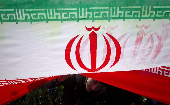 A demonstrator peeks from under an Iranian flag during a ceremony to mark the 33rd anniversary of the Islamic Revolution, in Tehran