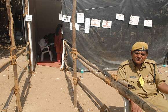 A lone policeman guards a nearly-empty polling booth
