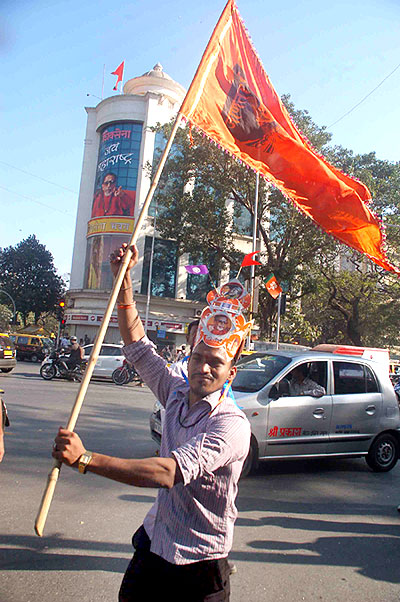 A Shiv Sena supporter celebrates the party's civic victory outside Sena Bhavan, the party's headquarters, in Mumbai
