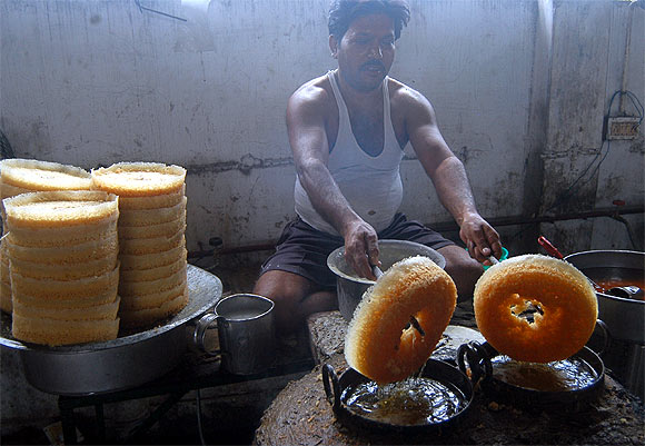 A worker prepares sweets at a shop in Lucknow