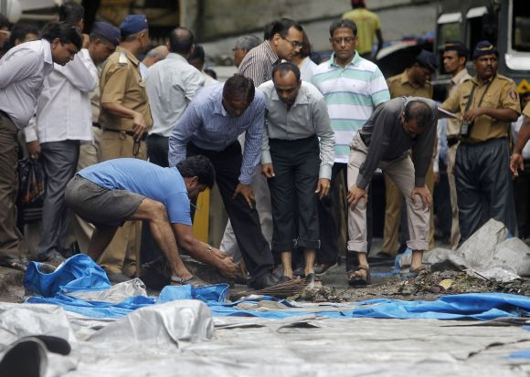A man moves debris during a clean-up operation near the Opera House, one of the sites of 13/7 triple explosions in Mumbai, suspected to be a handiwork of Indian Mujahideen