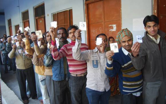Voters display they voter ID cards outside a polling booth