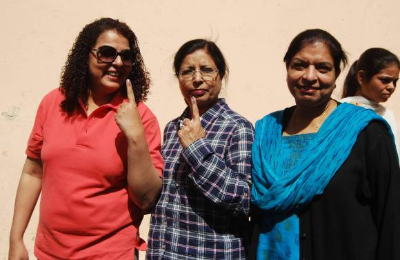 Voters show the indelible ink mark on their fingers after casting their vote