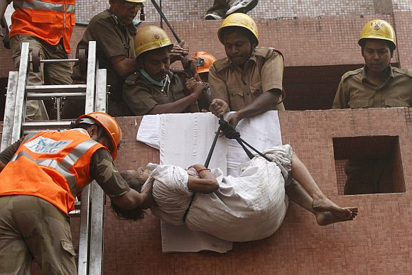 Firefighters evacuate a patient from AMRI hospital after it caught fire in Kolkata on December 9, 2011.